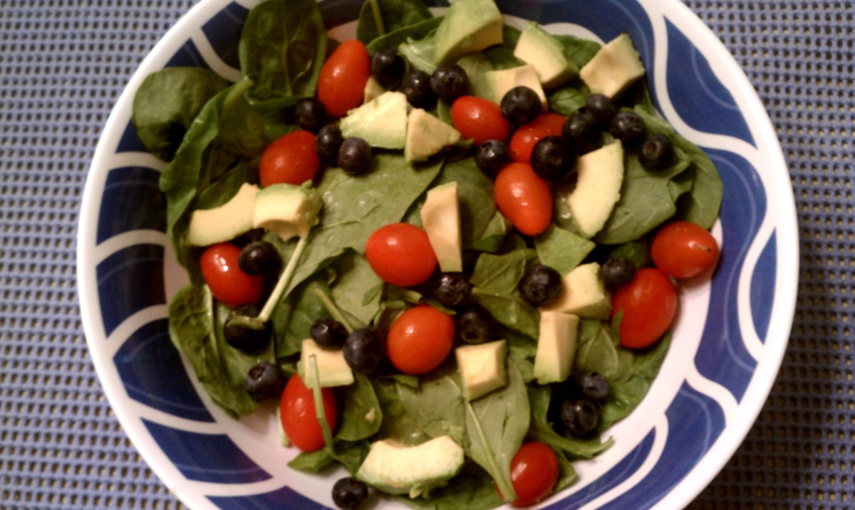 Spinach with tomatoes, avocado, and blueberries